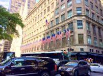 ニューヨークの建物の外に立ち並ぶアメリカの国旗の写真